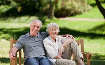 Couple sitting on bench with dental implants in cherry hills
